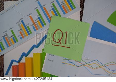 Q1 - 1st Quarter Period Write On Sticky Notes Isolated On Wooden Table. Stock Market Concept