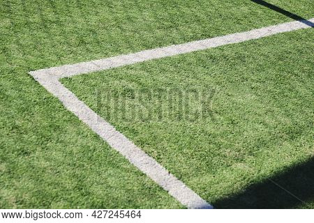 Synthetic Soccer Field, Green With White Lines, Located Outdoors. Sunlight Casts A Pattern Of Shadow