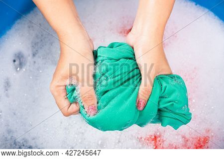Closeup Young Asian Woman Use Hands Washing Color Clothes In Basin. Female Squeeze Wring Out Wet Fab