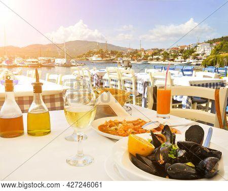 Seafood Dinner In Greek Restaurant On Seaside In Greece With Sun Shine
