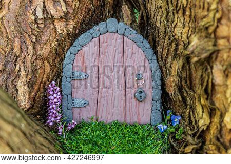 Little Fairy Tale Door Made From Clay In A Tree Trunk With Purple And Blue Flowers