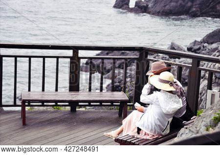 Couple On The Bench. Couple Sitting On The Bench With Lake View On Background.