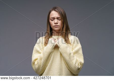 Portrait Of A Sad Young Woman Of Caucasian Ethnicity, Clenches Her Fists In A Yellow Sweater On A Gr
