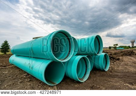 Stacked Water Main Pipe With Bell Fitting Next To An Exposed Trench For Installation