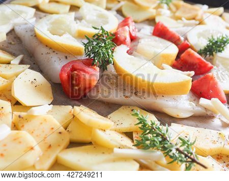 Cod Fillet Garnished With Thyme, Garlic And Tomatoes, Preparation Of A Healthy Dish. Healthy Food Co