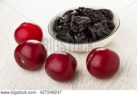 Heap Of Prunes In White Bowl, Few Ripe Plums On Wooden Table