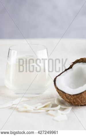Coconut Water Or Milk In A Glass, Coconut Chips And Half Of A Fresh And Juicy Coconut Lie Next To It