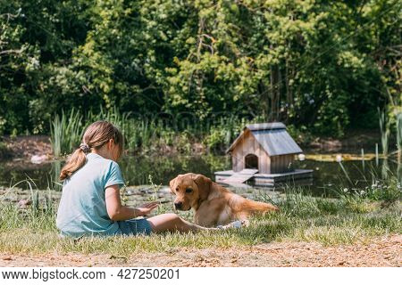 Friendship Of Animals And Children, People. Caucasian Girl Sits On The Bank Of A Pond, River And Pla