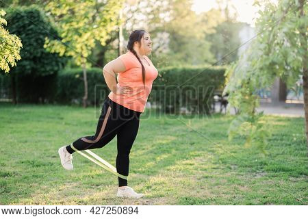 Body Positive. Fat Burning. Park Exercising. Band Workout. Cheerful Diligent Overweight Obese Woman