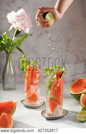 Two Glasses With Tall Long Drink With Watermelon, Lime Slices - And Mint - A Hand Pressing Lime Juic