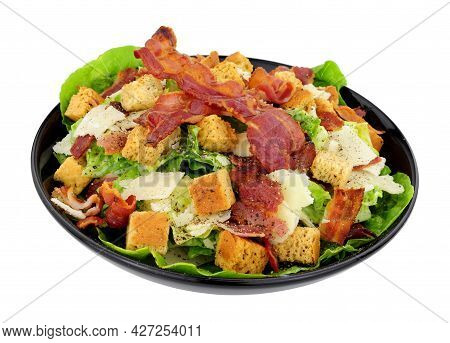 Bacon Caesar Salad With Romaine Lettuce And Parmesen Cheese Shavings Served In A Black Dish Isolated