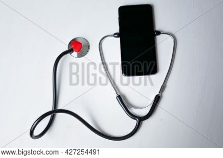 Smartphone Being Diagnosed With A Stethoscope Isolated On White Background With Copy Space. Phone Re