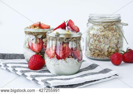 Healthy Breakfast. Oatmeal Granola With Greek Yogurt And Nuts Strawberry Muesli In Jars On Light Bac