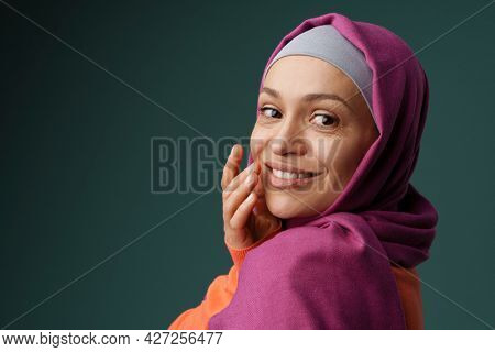 Middle eastern woman in hijab smiling and looking at camera isolated over grey background