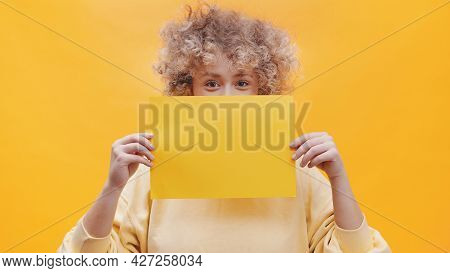 Girl Holding A Yellow Sheet Of Paper Covering Half Of Her Face With The Paper. Isolated Girl Over A