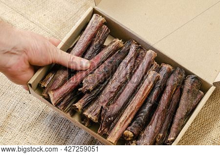 Hand Holds Cardboard Box Of Dog Treats. Sticks Of Dried Beef Esophagus. Chewing Treats For Pets. Ang