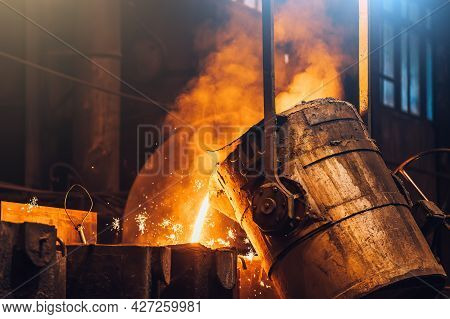 Liquid Metal Pouring Into Mold From Ladle In Foundry Metallurgical Plant, Heavy Industry.