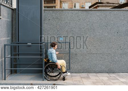 Mid aged smiling brunette disabled woman sitting in a wheelchair using accessible elevator for invalid persons