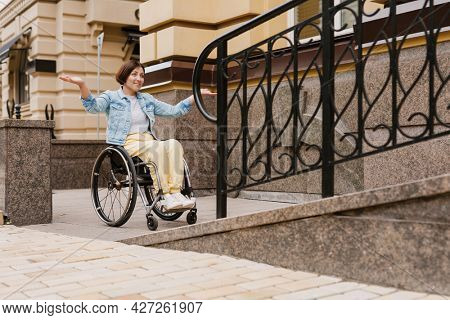 Mid aged happy brunette disabled woman sitting in a wheelchair standing near accessible entrance to the building