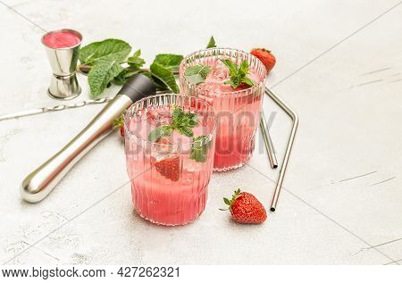 Refreshing Summer Drink With Strawberry Slices, Mint, And Ice In Glasses. Berry Mojito Cocktail Or M