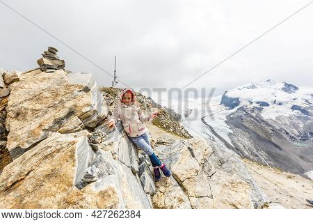 Children Hiking In Alps Mountains. Kids Look At Snow Covered Mountain. Spring Family Vacation. Littl