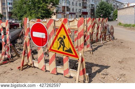 A Fence With A Road Works Sign And A Stop Sign Were Placed On The Road.