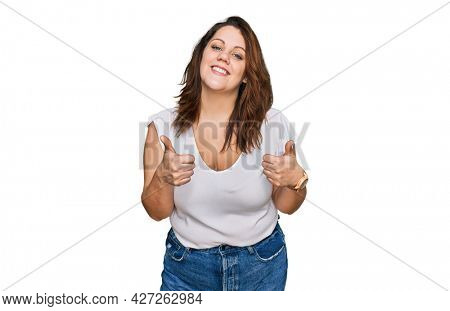Young plus size woman wearing casual white t shirt success sign doing positive gesture with hand, thumbs up smiling and happy. cheerful expression and winner gesture.