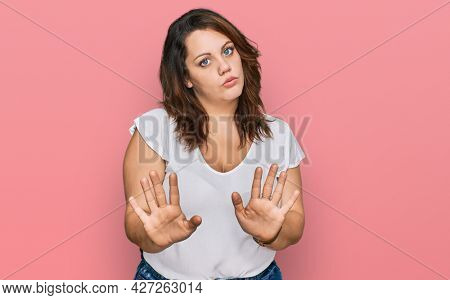 Young plus size woman wearing casual white t shirt moving away hands palms showing refusal and denial with afraid and disgusting expression. stop and forbidden.