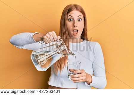 Young irish woman pouring water afraid and shocked with surprise and amazed expression, fear and excited face.