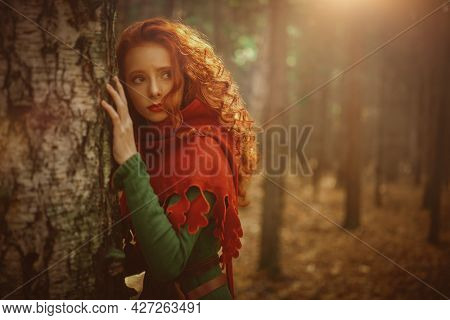 Beautiful red haired girl in a traditional green celtic dress and a red cloak is in forest. Historical reconstruction of ancient Celtic times.