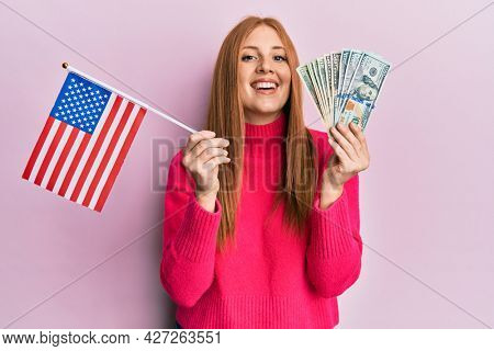 Young irish woman holding united states flag and dollars smiling and laughing hard out loud because funny crazy joke.