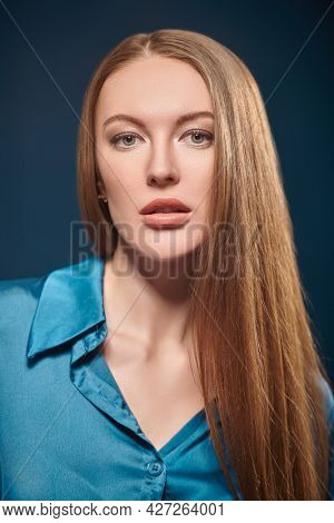 Beauty woman. Portrait of a gorgeous young woman with long straight hair on a dark blue background. Makeup and cosmetics.