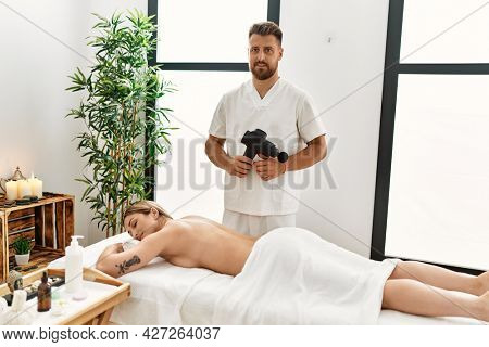 Young caucasian woman at physiotherapy clinic getting muscle massage by professional therapist. Physiotherapist man doing rehabilitation treatment with muscle gun