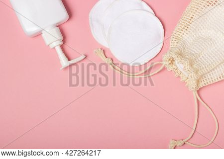 Cotton Reusable Make-up Remover Pads In A Cloth Bag And Face Wash And Cleanser On A Pink Background.