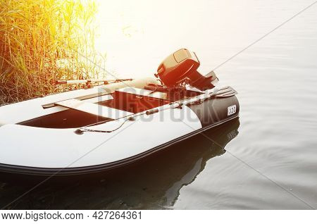 Inflatable Motor Boat On The Water Near The Coast At Sunrise Or Sunset, Outside. Calm Water, Selecti