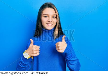 Young brunette girl wearing turtleneck sweater success sign doing positive gesture with hand, thumbs up smiling and happy. cheerful expression and winner gesture.
