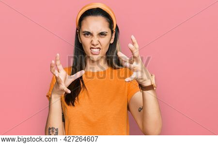 Young hispanic woman wearing casual clothes shouting frustrated with rage, hands trying to strangle, yelling mad