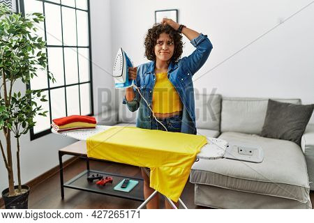 Young hispanic woman ironing clothes at home confuse and wondering about question. uncertain with doubt, thinking with hand on head. pensive concept.