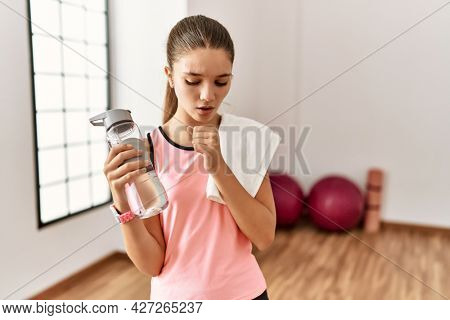 Young brunette teenager wearing sportswear holding water bottle feeling unwell and coughing as symptom for cold or bronchitis. health care concept.