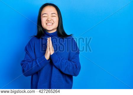 Young chinese girl wearing casual clothes begging and praying with hands together with hope expression on face very emotional and worried. begging.