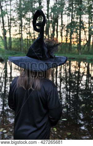 Little Witch In A Black Hat On The Shore Of A Pond In A Dense Dark Forest.children's Halloween. Magi