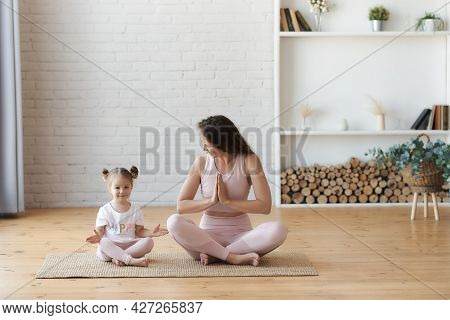 Smiling Young Mother In Pink Outfitt And Small Kid Girl Practicing Lotus Yoga With Mudra Hands Pose