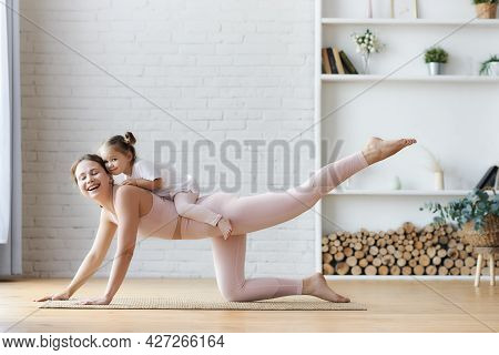 Young Smiling Active Mom And Little Baby Girl Daughter Exercising At Home, Having Fun Together, Foll