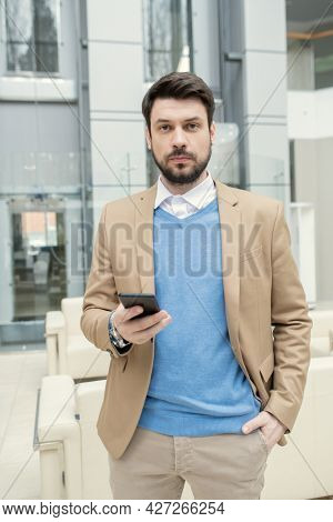 Portrait of young bearded businessman using mobile phone and looking at camera while standing at office hall