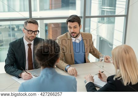 Young businessman talking to his partners while they sitting at the table and discussing new contract during business meeting at board room