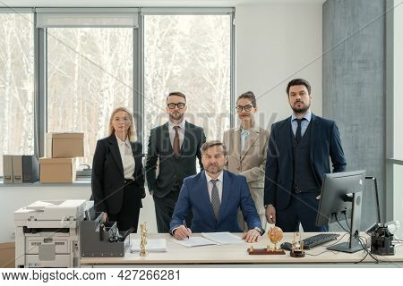 Portrait of group of business people looking at camera while standing at office with their leader in the centre at the table