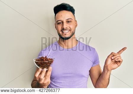 Young arab man holding raisins bowl smiling happy pointing with hand and finger to the side