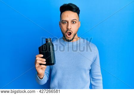 Young arab man holding motor oil bottle scared and amazed with open mouth for surprise, disbelief face