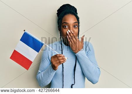 African american woman with braided hair holding france flag covering mouth with hand, shocked and afraid for mistake. surprised expression