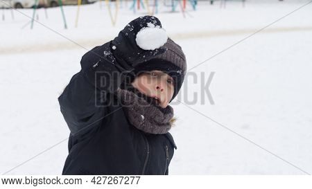 A Boy In Winter Clothes Aims A Lump Of Snow At A Friend In Winter On A Walk.